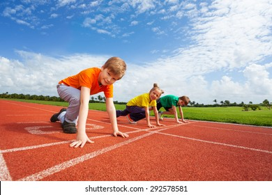 Two boys and girl on bended knee ready to run