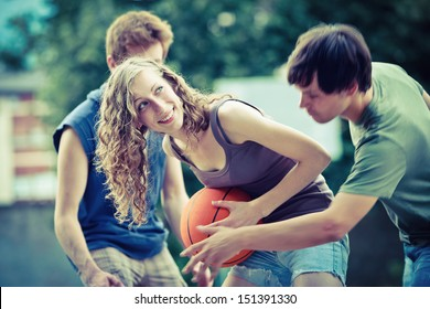 Two boys and a girl playing a game of basketball on an outdoor court.