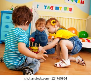 Two boys and girl playing with toy pyramid puzzle sitting on the floor in bedroom