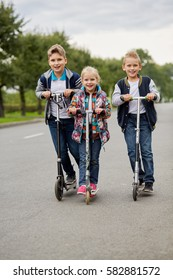 Two boys and girl ride on push scooters on road.