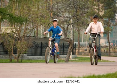 Two boys go for a drive on bicycles on park.
