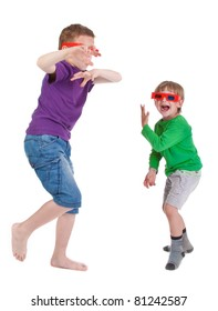 two boys having fun wearing 3D glasses on white background
