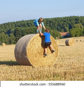 Two Boys Helping Each Other to Climb a Bale of Hay