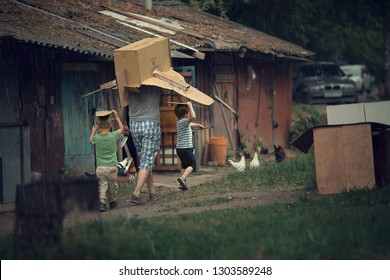 Two boys and his father are hiding from the summer rain under the box. Image with selective focus and toning