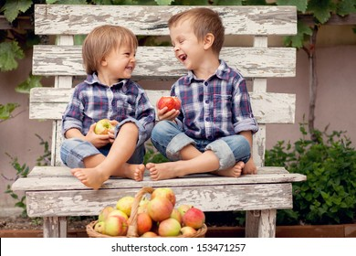 Two boys, holding apples