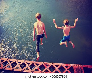 two boys jumping of an old train trestle bridge into a river toned with a retro vintage instagram filter effect app or action