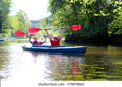Two boys kayaking on the river. Active happy friends, teenage schoolboys, having fun together enjoying adventurous experience with kayak on a sunny day during summer vacation