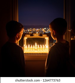 Two boys looking at the Menorah on the eighth night of Hanukkah