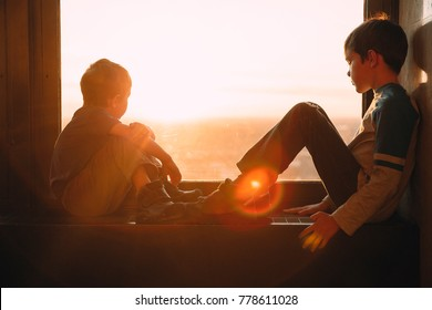 two boys looking out the window at sunset.