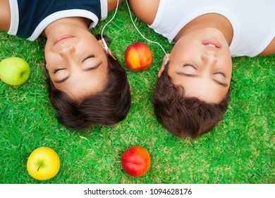 Two boys lying down on fresh green grass field and listening music from earphones, happy friends enjoying peaceful summer weekend outdoors