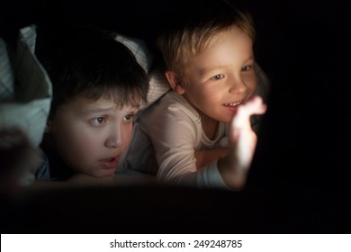 Two boys lying on bed under blanket at night. They watching movie or cartoon on pad. Screen enlighting their faces in darkness
