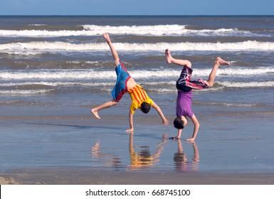 Two boys make a cartwhelll on the sandy beach.  Children rejoice, indulge, tinker