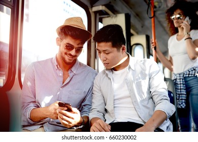 Two boys on the bus looking at phone.