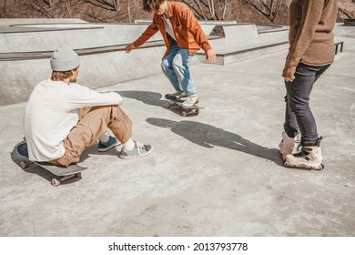 Two boys on skateboards and a girl on roller skates show each other what tricks they can do on the straight surface of a skatepark