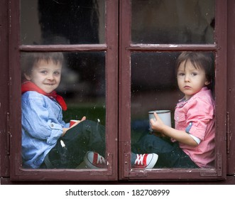 Two boys on the window, laughing and drinking tea, having fun