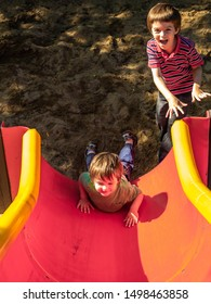 Two boys, one a toddler of about two years of age, the other a kindergartner about 5, are having fun on a playground. The younger slides backwards down a slide on his belly while his brother laughs.