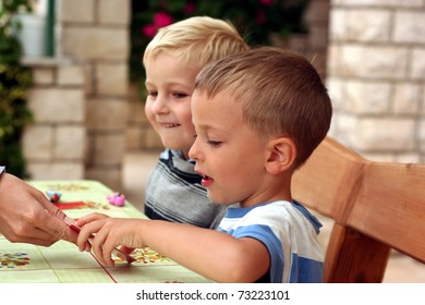 Two boys play a board game, one boy takes a card from a hand