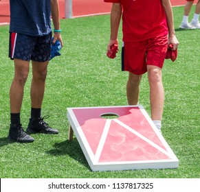 Two boys play corn hole during gym class on a green turf field in the sunshine.