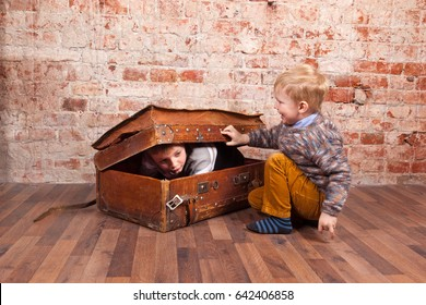 Two boys play hide and seek in the old vintage suitcase on the brick wall background