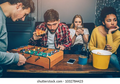 Two boys are playing board football game. They are very concentrated on it while girls are watching in the phone and feel boring. They don't like this game at all.