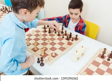 Two boys playing chess in tournament as sport moving pieces over the board