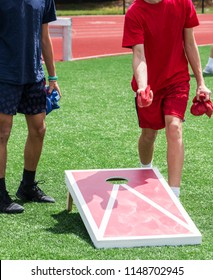 Two boys are playing a game of corn hole during a high school gym class on the turf.
