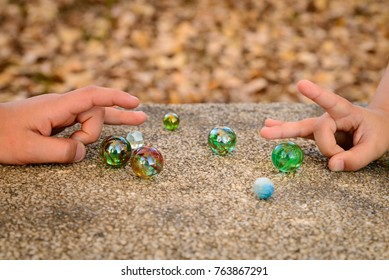 Two boys playing marbles