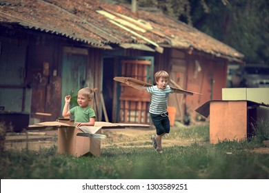 Two boys are playing in pilots with handmade cardboard box and ordinary sticks as a guns in summer. Image with selective focus and toning