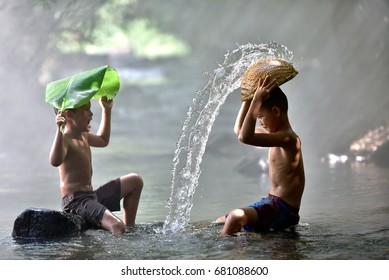 Two boys playing in a river in Thailand.