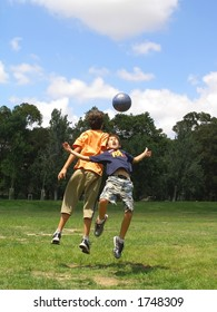 Two boys playing soccer in a green grass field with blue sky above
