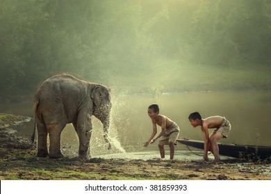 Two boys are playing splashing water with baby elephant at pond