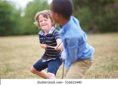 Two boys playing tug of war at the park