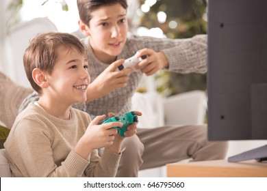 Two boys playing a video game on playstation at family dinner
