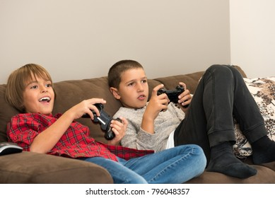 Two boys playing video games, holding remote controllers