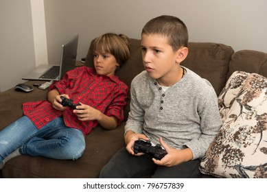 Two boys playing video games, lying on the  couch, holding remote controllers, gaming and competition