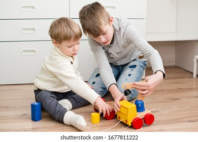 Two boys playing with wooden toy cars on the floor.