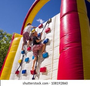 Two boys racing up balloon / inflatable climbing wall