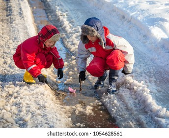 Two boys in rainboots playing with paper boat an the creek of melting snow at sunny spring day, outdoors