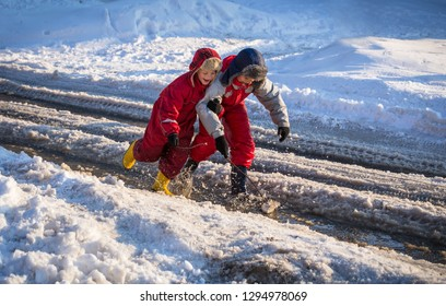 Two boys in rainboots playing with toy boat an the creek of melting snow at sunny spring day, outdoors