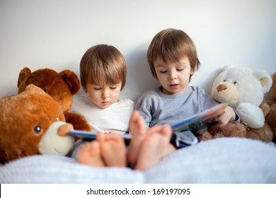 Two boys, reading a book, educating themselves