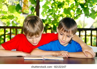 two boys reading a book at nature