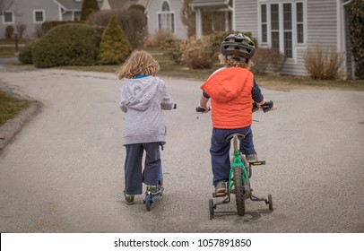 Two boys are riding a bike and a scooter alone a street in the suburbs. They are young children, in preschool. One child is wearing a helmet. The boy has training wheels. Learning to ride a bike.