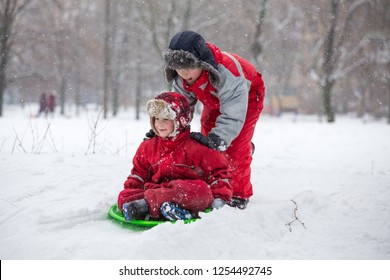 Two boys riding at the slide on snowy park, outdoors
