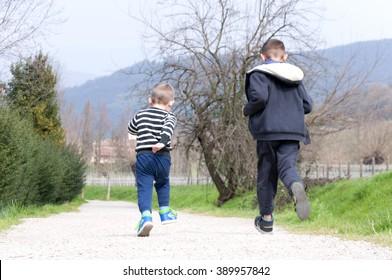 two boys run on rural road