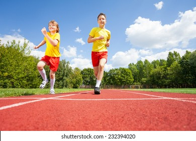 Two boys run while competing who is faster on stadium road in summer