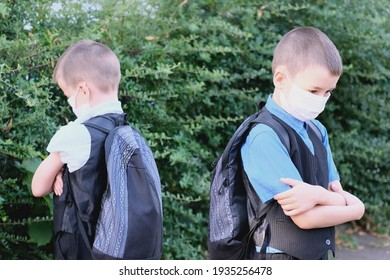 two boys, schoolchildren in black clothes with their faces covered by a medical mask quarreled, turned away, the concept of a quarrel and reconciliation of friends, back to school