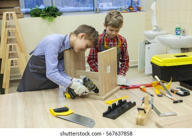 Two boys with screwdrivers and tools repairing wooden stool