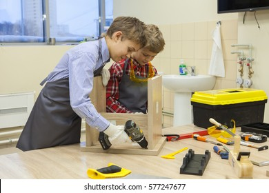 Two boys with screwdrivers and tools repairing wooden stool in workshop