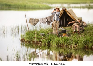 Two boys set up camp, and kindle the fire, sitting on the shore of the lake on a summer evening