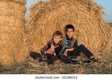 Two boys sit by the haystack